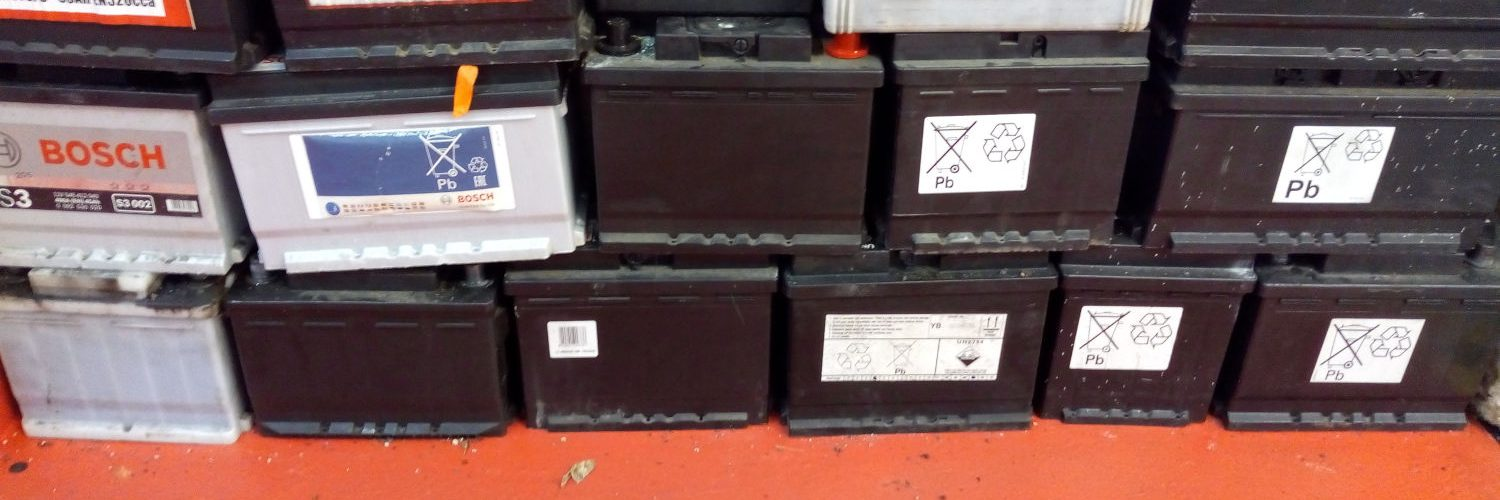 A stack of drained car batteries in the VFR Motor Services workshop